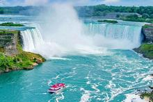 A sunny day at Niagara Falls, there is a red tourist boats approach the Falls