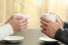 friends holding a cup of coffee, having a conversation