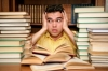 student looking worried with his head in his hands, surrounded by large stacks of books.