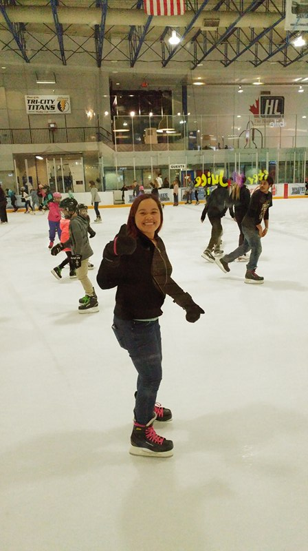 a student skating on the skating ring and did a thumb up, while others skate in the background