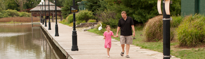 Father and daughter walking in Waterloo park.