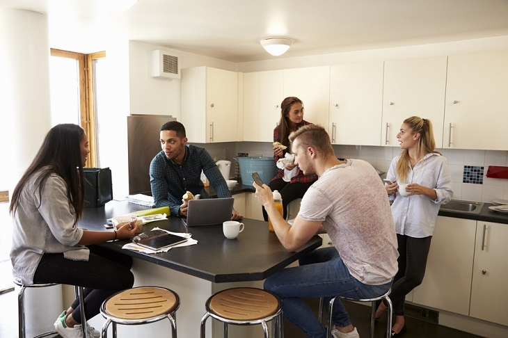 a group of students sitting or standing around the coffee table, socializing to each other