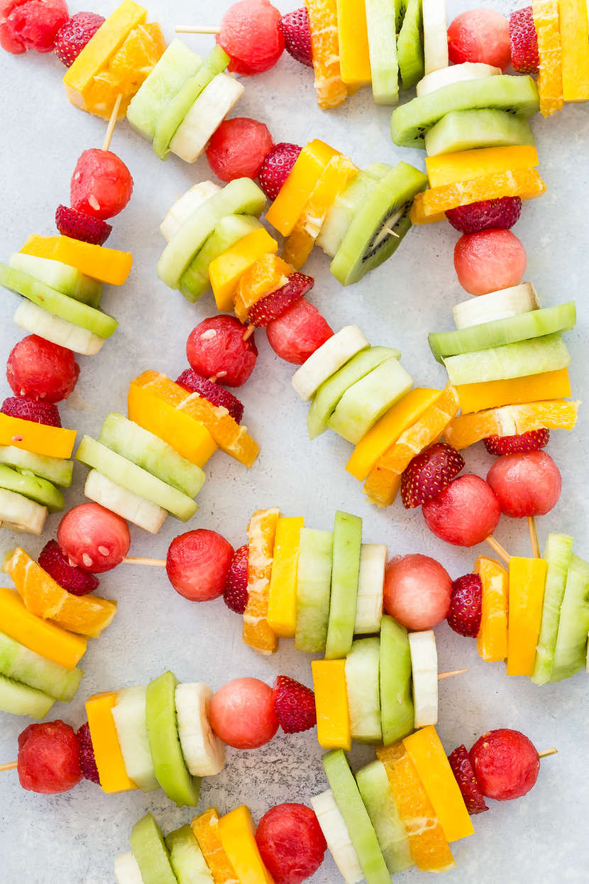 Many rainbow coloured fruit kabobs on a surface