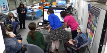 Photo of students around a computer.
