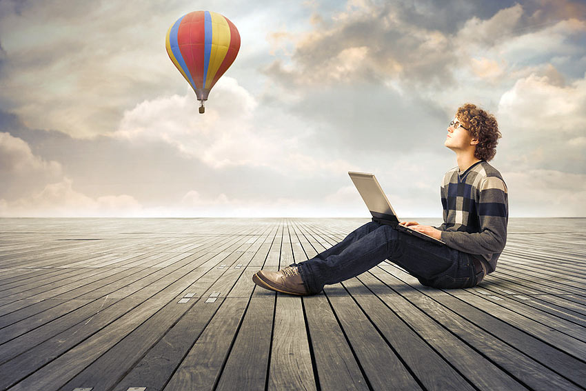 Photo of writer with laptop with hot-air balloon in background.