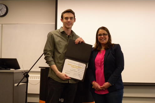 Trenton McNulty receives the Diaspora and Transnational Studies Prize from Lamees Al Ethari.
