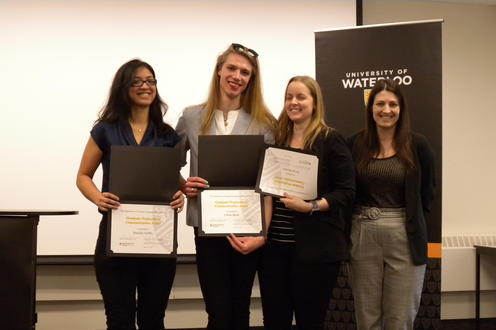 Devon Moriarty, Lillian Black, and Danielle Griffin receive the Graduate Professional Communication Award from  Megan Selinger