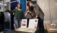 Photo of three students in front of a display about computers.