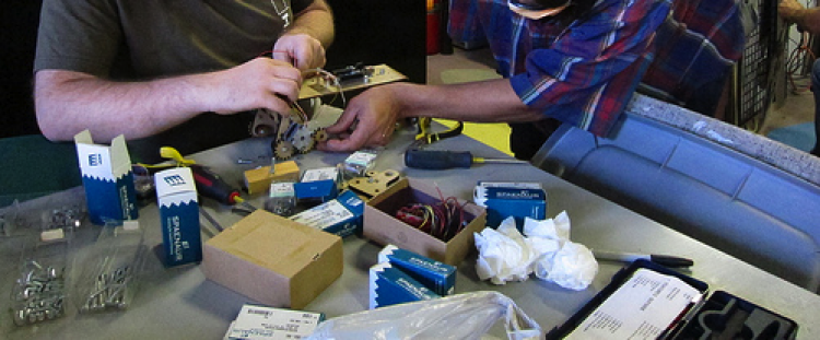 Photo of two people with small electronic components.
