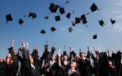 Photo of graduates throwing caps in the air.