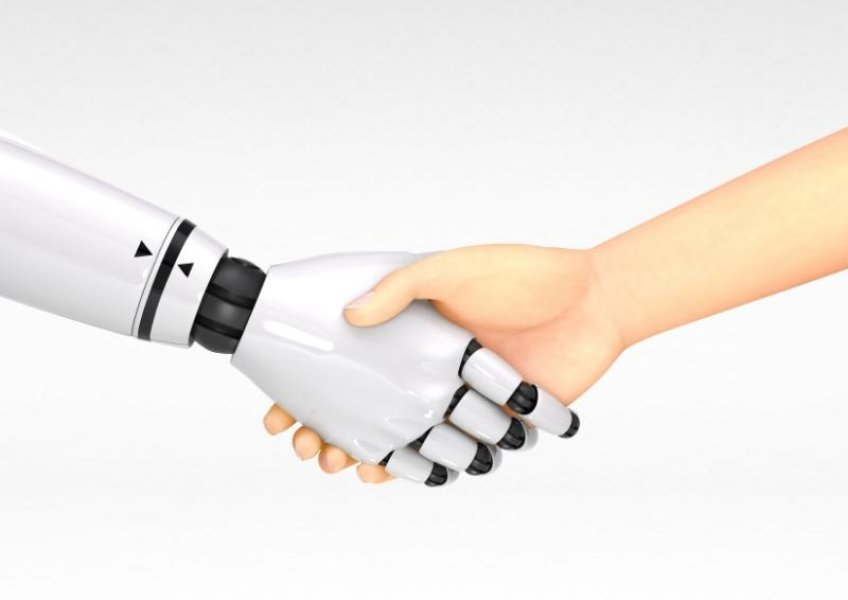 Picture of robot hand shaking human hand.