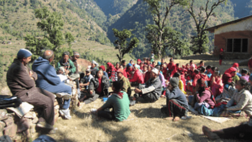 Group of Indigenous Nepalese sit on ground and stone wall having meeting