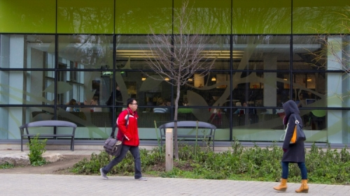 People walking past green and glass building