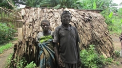 A man and wife Pygmy couple stand holding hands infront of a mud hut.
