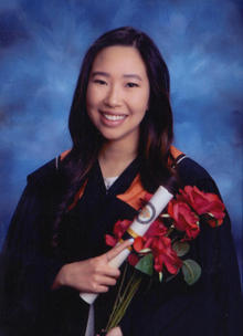 Valedictorian Chantelle Young posing for a graduation photo with a diploma and flowers