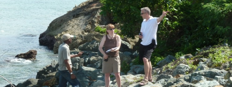 Professor Dan Scott and two other people on a rocky beach observing the scene.