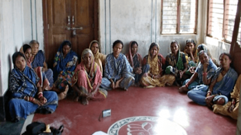 Group of Indian women sit on floor in a half circle
