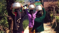 Three Indian women in colorful outfits carrying water on their heads
