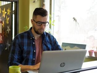 University student working on laptop in coffee shop