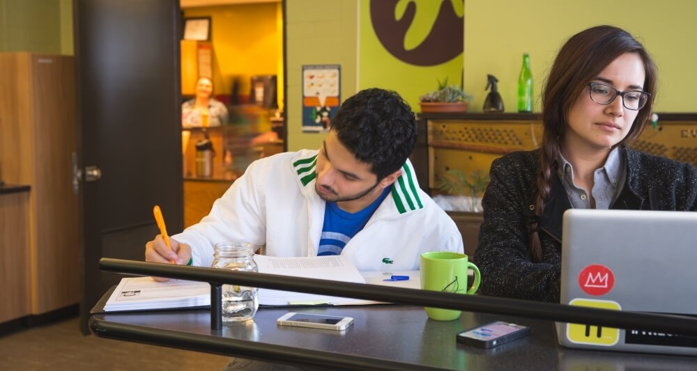 Two students doing school work in a cafe