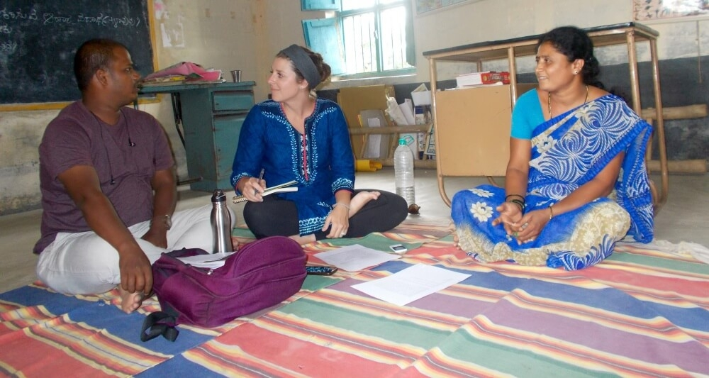 Three people sit on a cotton rug on the floor on a classroom in India