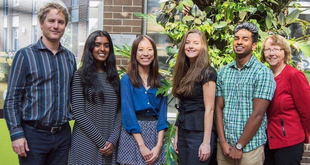 Four students smiling with Dean and associate dean