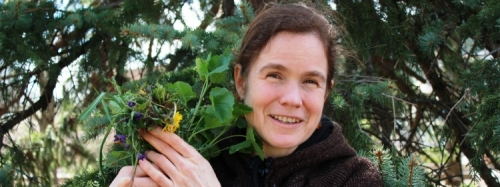 Woman holds a bouquet of wild plants.