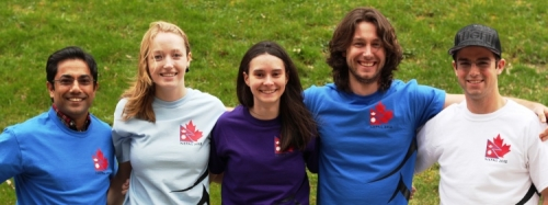 A professor and four students pose in T-shirts featuring a Nepalese flag and Canadian maple leaf.