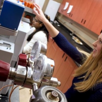 Student with long blonde hair reaches for sample tubes on top of machine. Gauges and dials are in foreground.