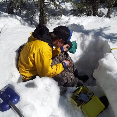 Researcher sitting in snow pit with instruments
