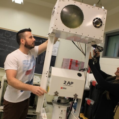 Two student stand on either side of large, white machine