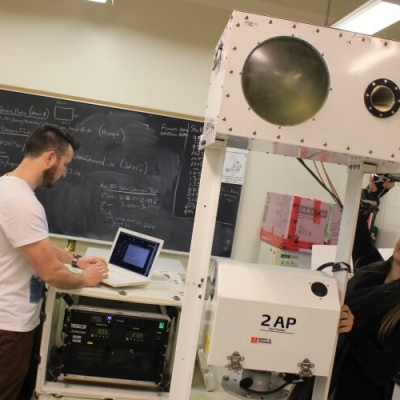 Female student drills side of large device while male student works on laptop