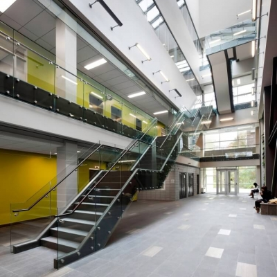 A modern, light-filled atrium with a feature 4-story staircase, skylight and glass railings.
