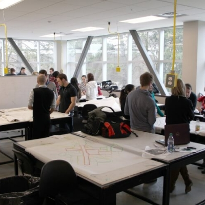 A large, light filled design studios with many spacious work tables and students working on projects.