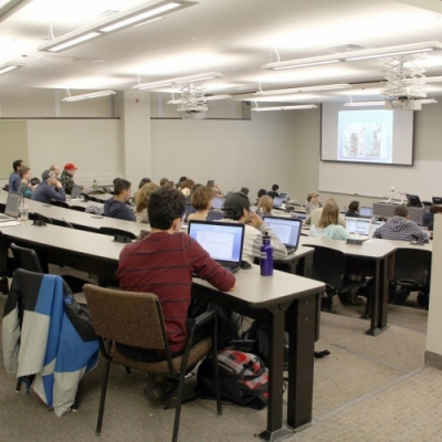 A large, modern, tiered lecture hall full of students.