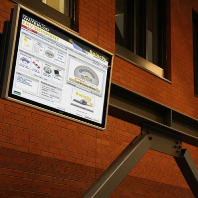 Suspended digital display showing meters and graphs that indicate building's energy use.