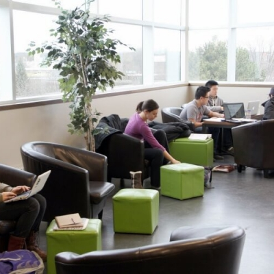 Students sitting in comfortable chairs in front of a bank of windows.