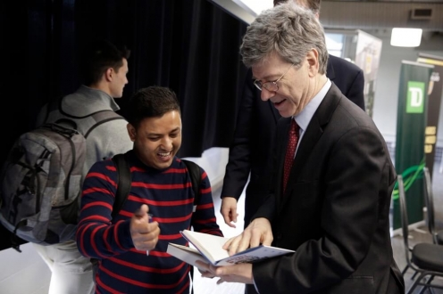 Man in dark suit signing a book for a fan