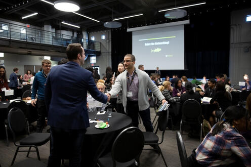 Alumni volunteers shaking students hand at networking event