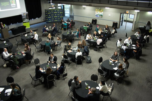 Overhead shot of tables of alumni volunteers and students at networking event