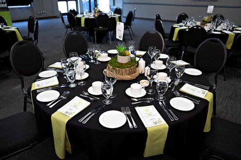 A decorated table with plates, a centrepiece, and menus