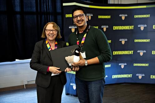Dean Jean and a student awardee holding up a plush goose prize