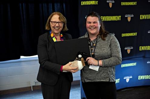 Dean Jean and a student awardee holding up her plush goose prize