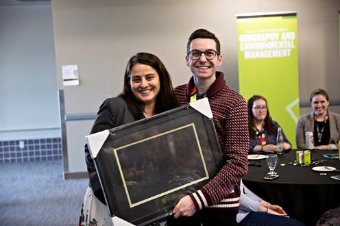 Maryam and a student awardee holding up a photo frame