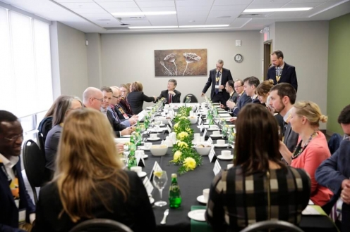 Diverse group of professionals seated around Boardroom table for lunch