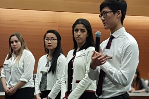 Four students in a row, speaking to judges