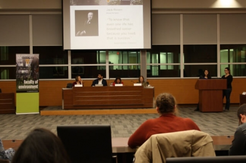 Panel of 4 judges at front of room as woman speaks at podium