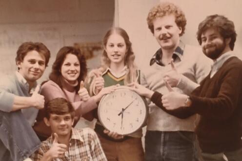 Planning Class of '81 holding up a clock after a long night of PLAN 300