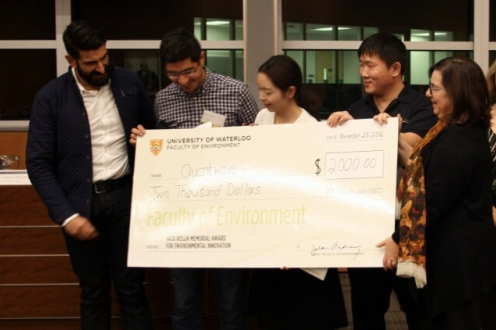 Three students hold giant cheque, along with two judges