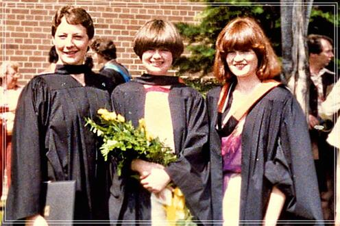 Three students standing outside in graduation gowns. From left to right: Gillian Mason, Louise Riddel, Lee Anne Doyle.